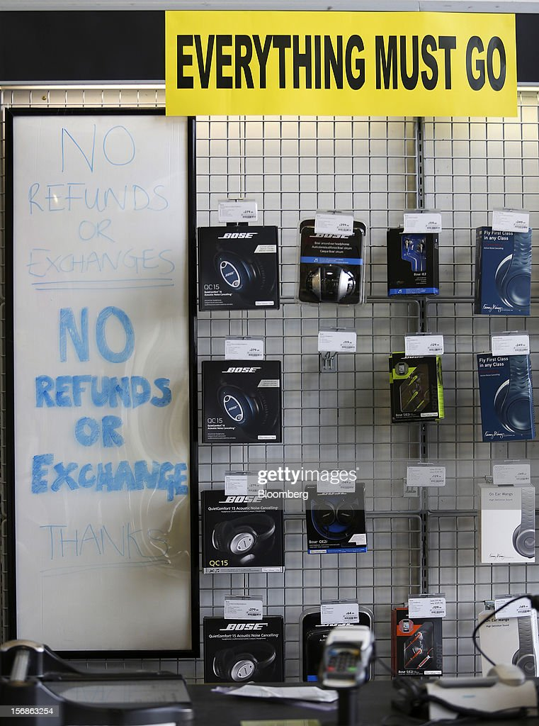 Signs alerting customers that 'Everything Must Go' and 'No Refunds Or Exchanges' sit next to headphones inside a Comet electronics store in Slough, U.K., on Friday, Nov. 23, 2012. Comet, a U.K. electronics chain, appointed Deloitte LLP as insolvency administrator, less than a year after being bought by private-equity firm OpCapita LLP. Photographer: Chris Ratcliffe/Bloomberg via Getty Images