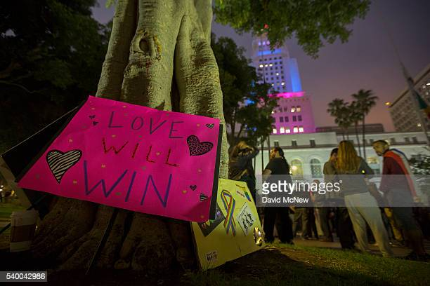 Signs are left on a tree near City Hall which is lit in the colors of the rainbow flag to honor the LGBT victims of the worst mass shooing in United...