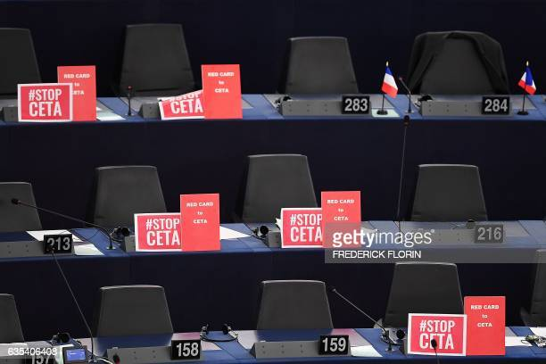Signs are pictured near empty seats during a voting session on the EUCanada Comprehensive Economic and Trade Agreement at the European Parliament in...