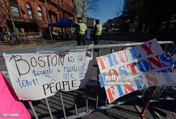 Signs are placed at a makeshift memorial for victims near the finish line of the Boston Marathon bombings two days after the second suspect was...