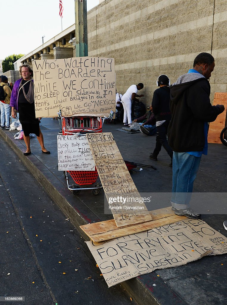 Signs displayed on a public sidewalk as homeless people rest February 28, 2013 in downtown skid row area of Los Angeles, California. Los Angeles officials will ask U.S. Supreme Court to overturn a lower-court ruling preventing the destruction and random seizures of belongings that homeless people leave temporarily unatteneded on public sidewalks. The lower court ruling has hindered cleanup efforts.