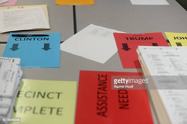 Signs for presidential candidates line tables as volunteers and city officials participate in a recount at the Oakland Schools Conference Center on...