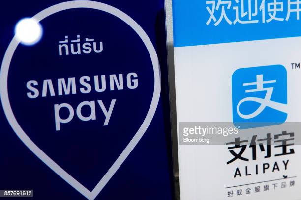 Signs for Samsung Electronics Co's Samsung pay and Ant Financial Services Group's Alipay an affiliate of Alibaba Group Holding Ltd are displayed at a...