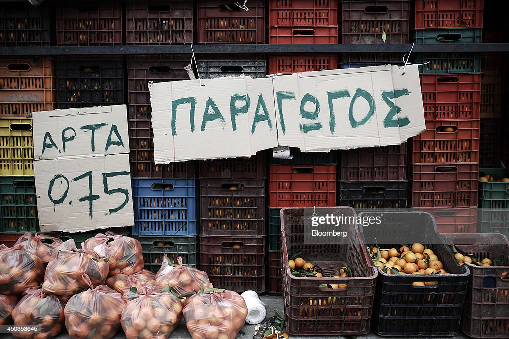 Signs hang from the back of a truck as crates of mandarins sit on display at a farmers' market in Thessaloniki, Greece, on Saturday, Nov. 16, 2013. Greek Prime Minister Antonis Samaras, who survived a no-confidence vote on Nov. 11 with his parliamentary majority reduced to four, is trumpeting the first economic growth in seven years for 2014. Photographer: Konstantinos Tsakalidis/Bloomberg via Getty Images