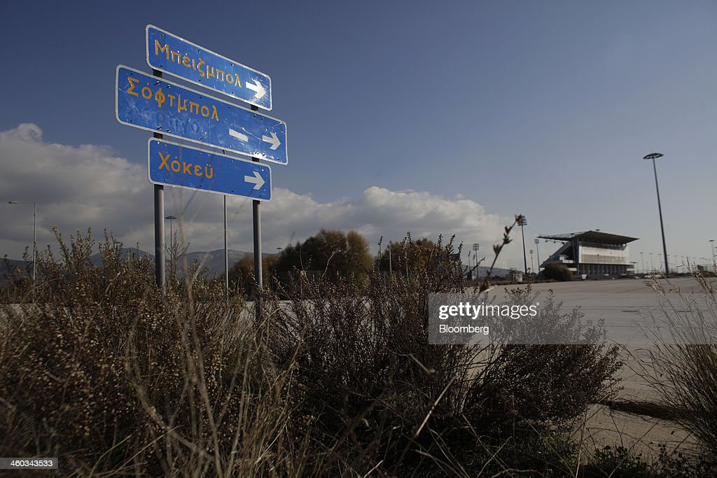 Signs indicate the direction to the Olympic fields for baseball, softball and hockey at the former Athens International Airport in the Hellenikon district of Athens, Greece, on Friday, Dec. 3, 2014. Hellenikon is the largest of Greece's land development projects, three times the size of the Principality of Monaco. Photographer: Kostas Tsironis/Bloomberg via Getty Images