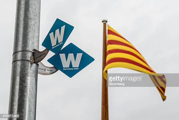 'W' signs mark the location of a municipal city WiFi signal point beside a Catalan flag on a street in Barcelona Spain on Friday Feb 21 2014 A smart...