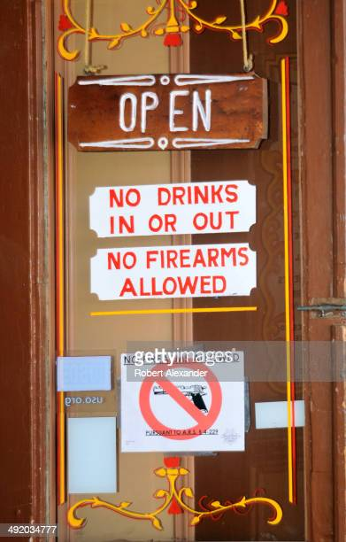 Signs on a saloon door advise customers that no guns are allowed inside the business in historic Tombstone Arizona known as 'The Town Too Tough to...