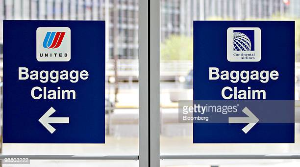 Signs point to baggage claim areas for Continental Airlines right and United Airlines at O'Hare International Airport in Chicago Illinois US on...
