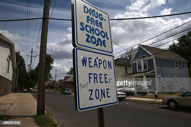 Signs reading 'Drugfree School Zone' and 'Weapon Free Zone' stand along a notorious highcrime neighborhood August 27 2015 in Pleasantville Atlantic...