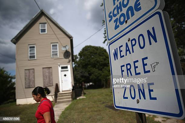 Signs reading 'Drugfree School Zone' and 'Weapon Free Zone' stand in front of an abandoned home along a notorious highcrime neighborhood August 27...