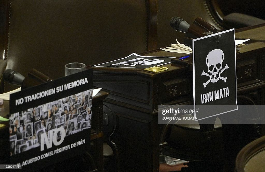 Signs reading 'Iran Kills' (R) and 'Dont betray their memory, NO to the agreement with Iran's regime' are displaying on the opposition deputies desks at the chamber of deputies in Buenos Aires on February 27, 2013, as they discuss the possibility of an agreement with Iran to establish a truth commission over a terrorist attack that took place in 1994. Eight Iranian nationals are still wanted in connection with the bombing of the Argentine Israelite Mutual Association (AMIA) that left a toll of 85 dead and 300 wounded. AFP PHOTO / Juan Mabromata