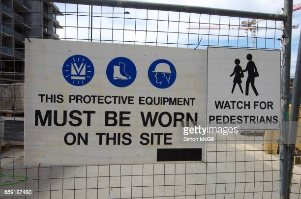 Signs reminding construction workers to wear protective equipment, and watch out for pedestrians, on a construction site for a residential apartment building