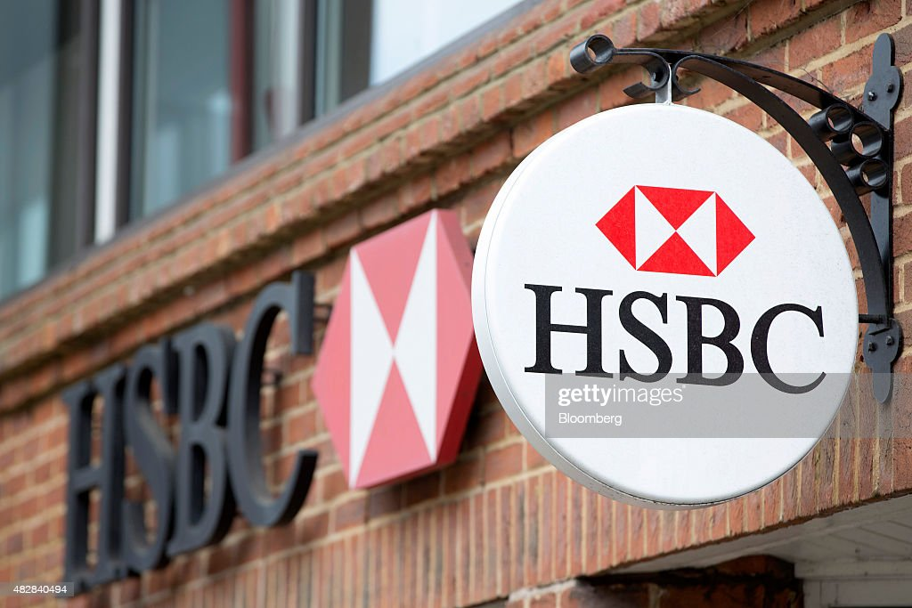 Signs sit above a HSBC bank, operated by HSBC Holdings Plc, in Guildford, U.K., on Monday, Aug. 3, 2015. HSBC, Europe's largest bank, reported an 18 percent climb in second-quarter profit amid higher trading income and gains from a sale of shares in China's Industrial Bank Co. Photographer: Jason Alden/Bloomberg via Getty Images
