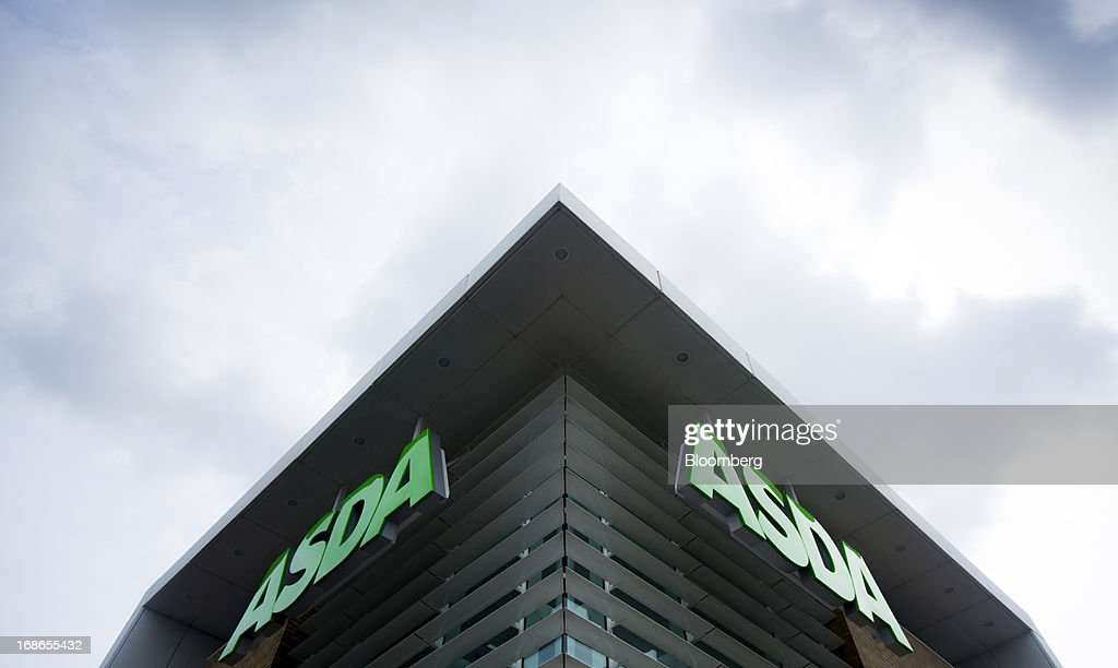 Signs sit above the entrance to an Asda supermarket store, operated by Wal-Mart Stores Inc., in the Merton borough of London, U.K., on Monday, May 13, 2013. Asda, the U.K. supermarket chain owned by Wal-Mart Stores Inc., said sales rose 4.5 percent last year and it's investing 700 million pounds ($1 billion) into stores and online operations. Photographer: Jason Alden/Bloomberg via Getty Images
