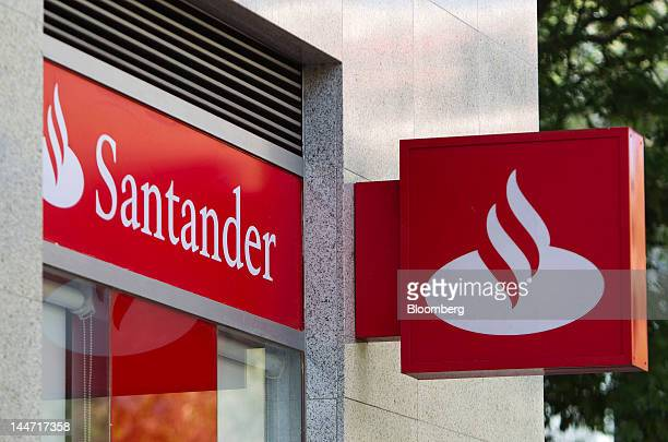 Signs sit outside a Banco Santander SA bank branch in Madrid Spain on Friday May 18 2012 Banco Santander SA and Banco Bilbao Vizcaya Argentaria SA...