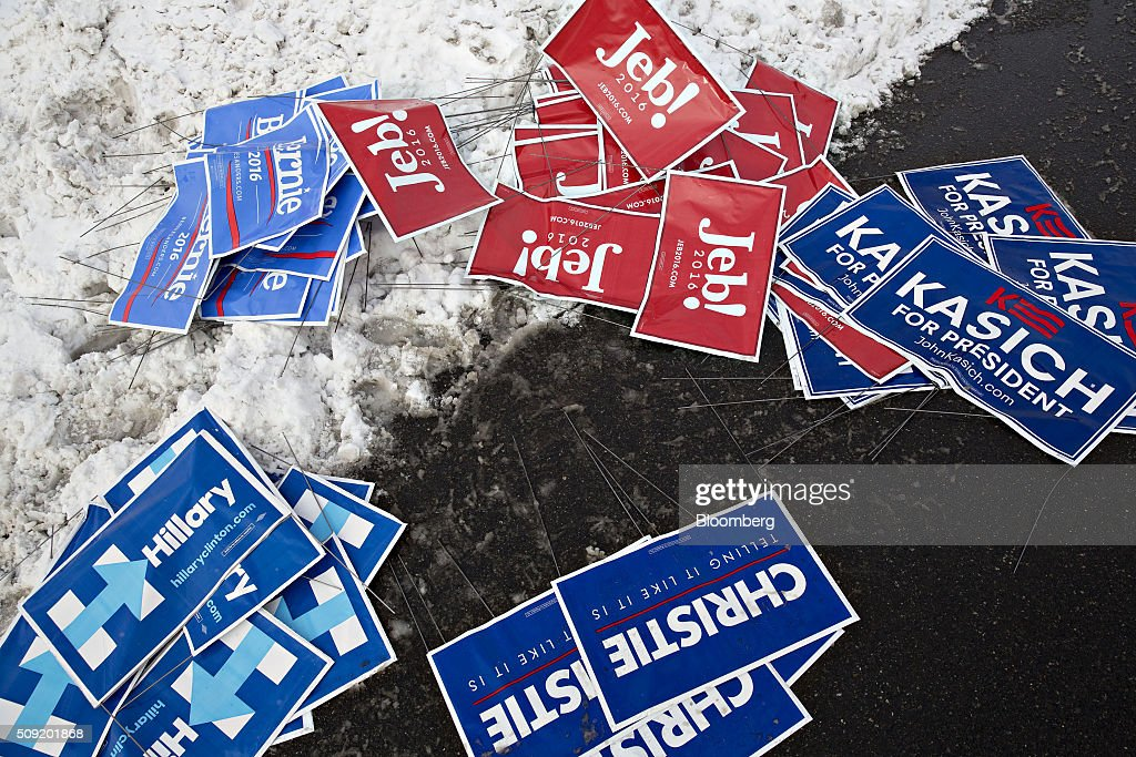 Signs supporting 2016 presidential candidates Jeb Bush, former governor of Florida, John Kasich, governor of Ohio, Chris Christie, governor of New Jersey, Hillary Clinton, former Secretary of State, and Senator Bernie Sanders, an independent from Vermont, sit in a pile outside a polling station in Bedford, New Hampshire, U.S., on Tuesday, Feb. 9, 2016. Voters in New Hampshire took to the polls today in the nation's first primary in the U.S. presidential race. Photographer: Daniel Acker/Bloomberg via Getty Images
