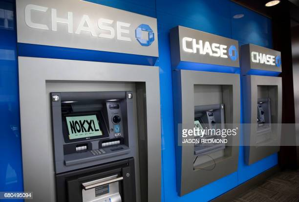 Signs taped to ATMs read 'No KXL' as indigenous leaders and climate activists disrupt business at a Chase Bank branch to protest funding tar sands...
