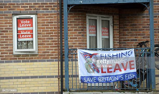 Signs to leave the EU are attached to windows and a balcony of a block of flats in Hove near Brighton southern England on June 23 2016 Millions of...