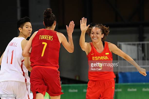 Sijing Huang of China looks on as Alba Torrens and Laia Palau of Spain celebrate scoring in the Women's Basketball Preliminary Round Group B match...