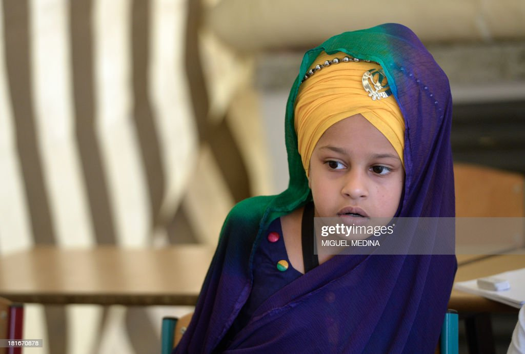 Sikh child attends on September 22, 2013 a language class at the largest gurdwara or Sikh temple in France, located in the Paris suburb of Bobigny. France's Sikh community is ramping up a campaign for the turban to be allowed in state-funded schools amid moves to reinforce a 2004 law banning pupils from sporting religious symbols. The contentious issue pits the cherished French principle of secularity in public life and institutions against the essence of the Sikh religion, which requires followers to keep long hair as a mark of their faith and piety and a turban to cover the tresses, worn as a bun on the top of the head.