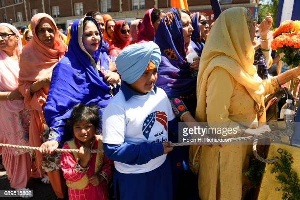 Sikh children and women line up behind the float carrying the Guru Granth Sahib the Sikh holy book during the second annual American Sikh day parade...