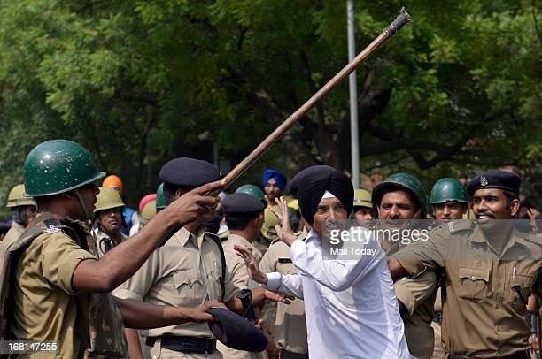 Sikh community members scuffle with policemen as they shouts anti government slogans during a demonstration against the acquittal of Congress...