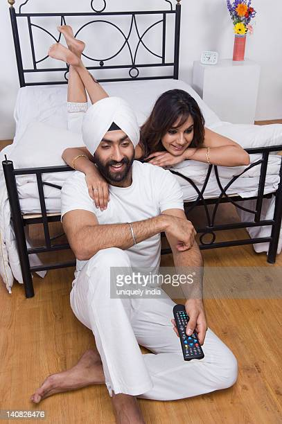 Sikh couple watching TV in the bedroom