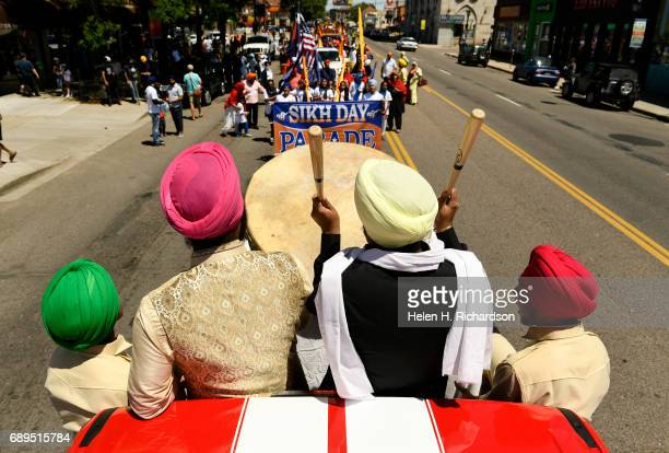 Sikh drummers Parvinder Singh second from left and his nephew Sahibpreet Singh second from right play a Nagara drum as they ride in the second annual...