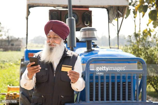 Sikh farmer using credit card and mobile phone