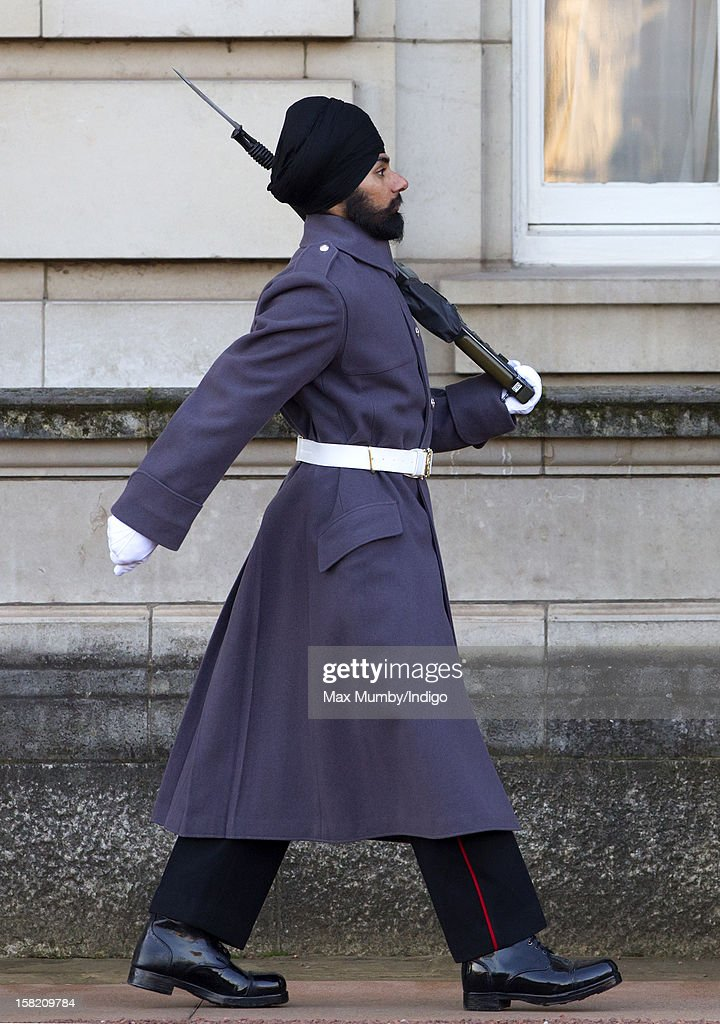 Sikh Guardsman Jatenderpal Singh Bhullar, a soldier in the Scots Guards, marches by his sentry box whilst on guard duty in the forecourt of Buckingham Palace on December 11, 2012 in London, England. Guardsman Bhullar is the first Sikh Guardsman to wear a turban rather than the traditional bearskin whilst on guard duty.