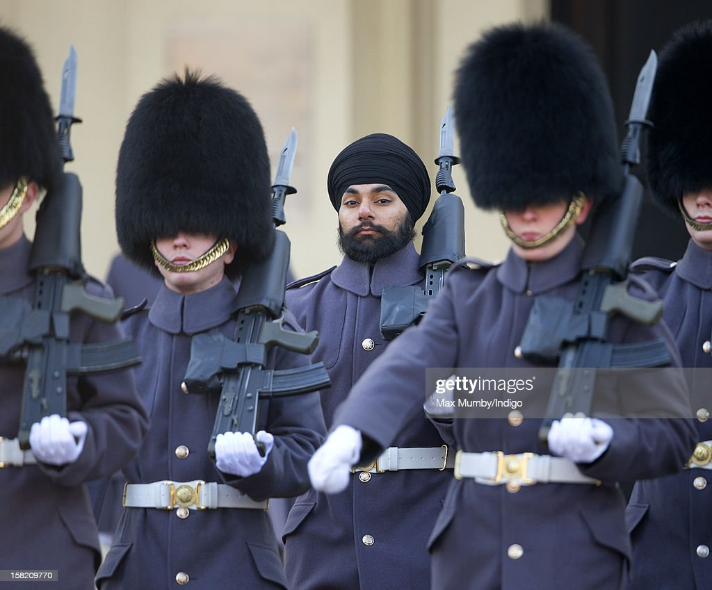 Sikh Guardsman Jatenderpal Singh Bhullar (C), a soldier in the Scots Guards, forms up with his fellow soldiers on the parade ground of Wellington Barracks before going on guard duty in the forecourt of Buckingham Palace on December 11, 2012 in London, England. Guardsman Bhullar is the first Sikh Guardsman to wear a turban rather than the traditional bearskin whilst on guard duty.