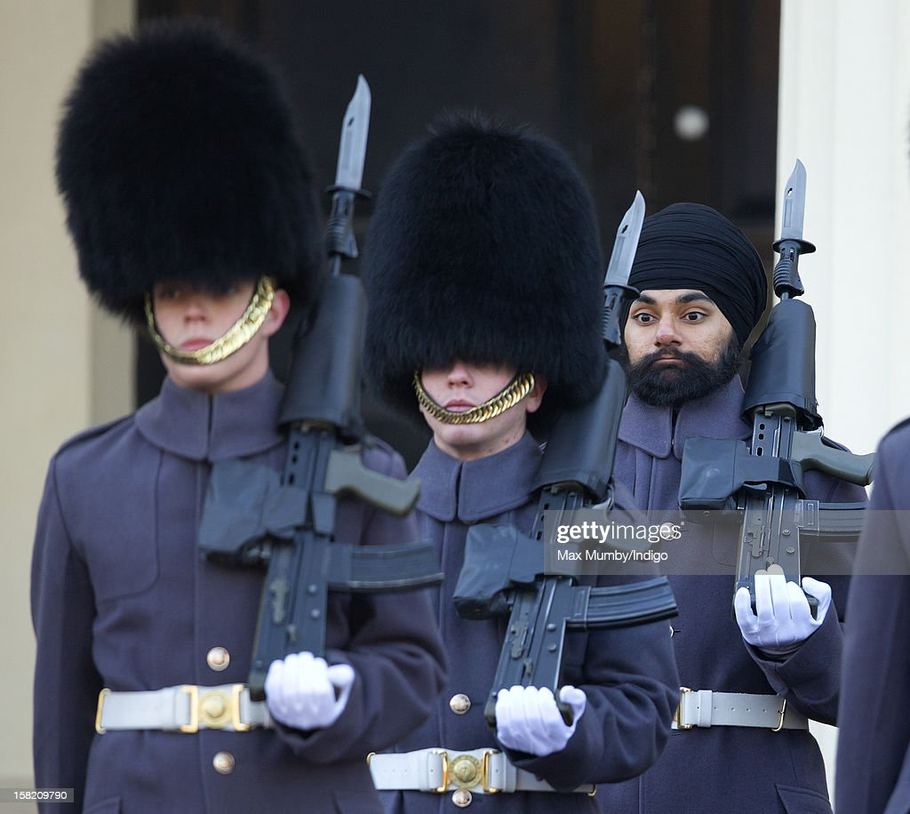 Sikh Guardsman Jatenderpal Singh Bhullar (R), a soldier in the Scots Guards, forms up with his fellow soldiers on the parade ground of Wellington Barracks before going on guard duty in the forecourt of Buckingham Palace on December 11, 2012 in London, England. Guardsman Bhullar is the first Sikh Guardsman to wear a turban rather than the traditional bearskin whilst on guard duty.