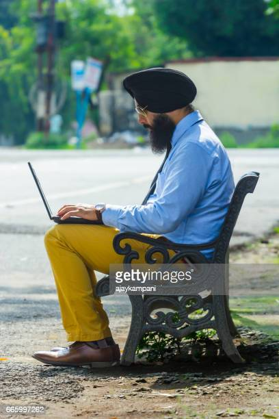 Sikh man relaxing on the bench using his laptop