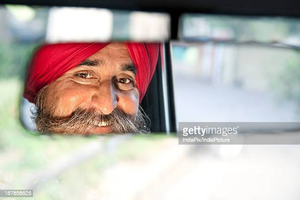 Sikh taxi driver looking into the rear view mirror