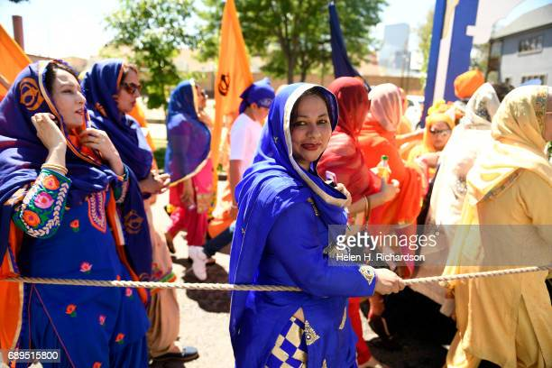 Sikh women line up behind the float carrying the Guru Granth Sahib the Sikh holy book and sing as they march during the second annual American Sikh...