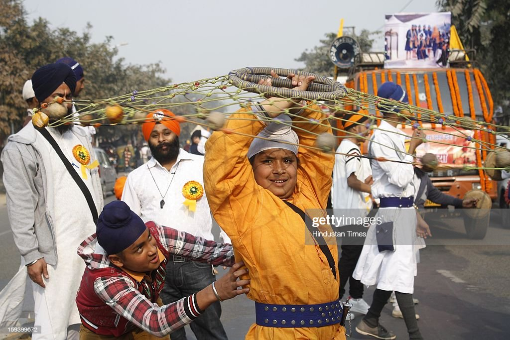 Sikh youngsters perform on the occasion of Prakash Parv of the 10th Guru of Sikh Community Guru Gobind Singh during a religious procession at Sector 25, on January 13, 2013 in Noida, India.