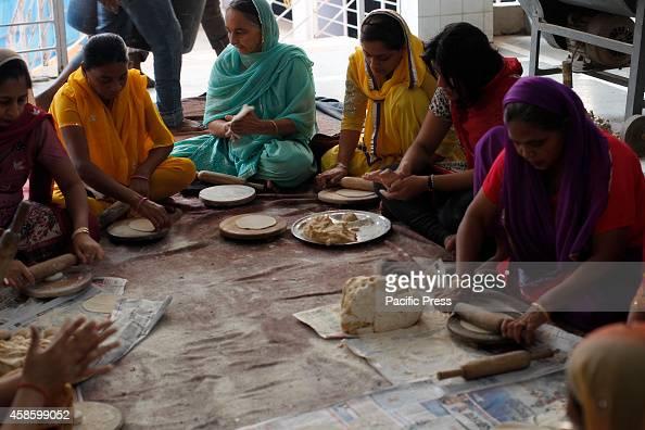 Sikha devotees prepare roti for langar on the occasion of Guru Nanak birth anniversary at a Gurdwara in Allahabad