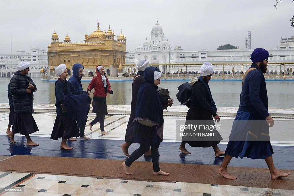 US Sikhs and students of The Miri Piri Academy walk to pay their respects during a rain shower at the Sikh Shrine Golden Temple in Amritsar on January 18, 2013. Sikhs are celebrating the 348th Birth Anniversary of the tenth Sikh Guru Gobind Singh.