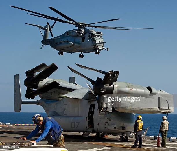 A Sikorsky CH53E Super Stallion Iron Horse helo takes off from the deck of the USS Wasp over a Bell Boeing V22 Osprey with it's props nondeployed...