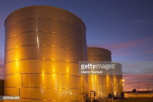 Silage storage tanks illuminated at night