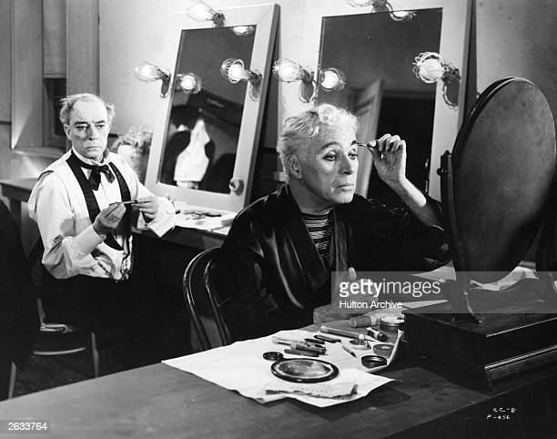 Silent comics Charlie Chaplin and Buster Keaton putting their stage makeup on in a scene from the United Artists film 'Limelight' written directed...