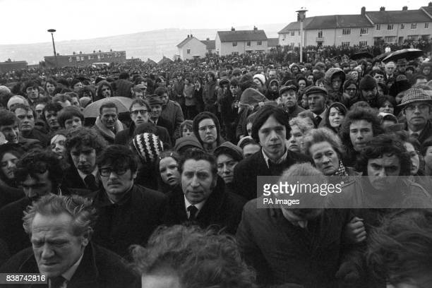 A silent crowd form a cordon 10 or more deep lining both sides of the 250 yards of road leading from St Mary's Church Creggan Hill to the cemetery to...