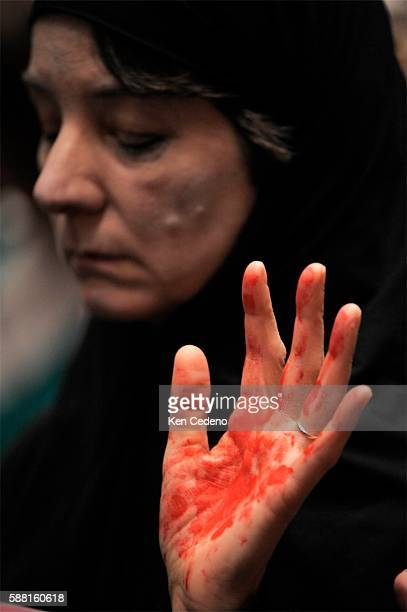 A silent protester holds up her hand covered in red paint during a hearing held by the Senate Armed Services Committee on Capitol Hill in Washington...