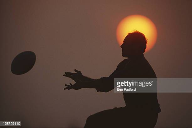 Silhouete of a player passing the ball framed by the sun on 2nd December 1990 during the Dubai Rugby Sevens tournament at the Dubai Exiles Rugby...