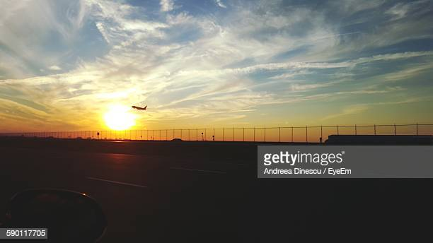 Silhouette Airplane Flying Against Sunset Sky Seen From Highway