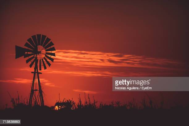 Silhouette American-Style Windmill On Field Against Red Sky During Sunset