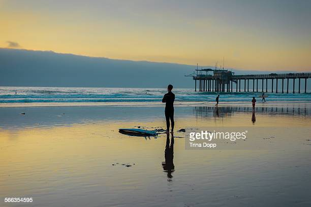 Silhouette and reflection of a surfer and his surfboard at sunset near Scripps Pier at Scripps Beach in La Jolla California 09/12/14