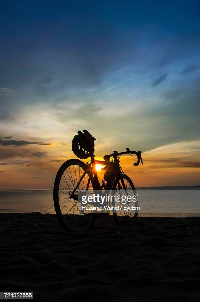 Silhouette Bicycle On Beach At Sunset