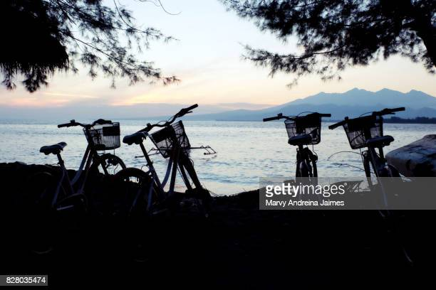 Silhouette bicycles parked at beach during sunrise