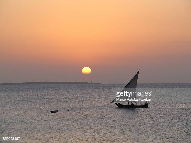 Silhouette Boat Sailing In Sea At Sunset